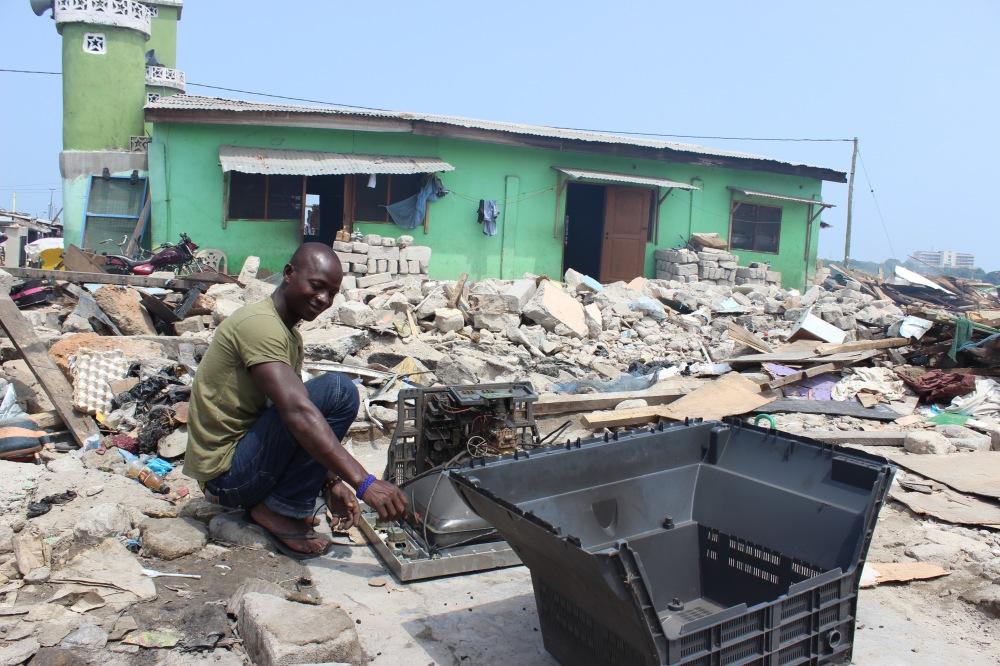 Als Militär und Polizei den Slum räumten, verlor Hudu seine Hütte. Auf seiner Veranda zerlegt er einen alten Fernseher.
